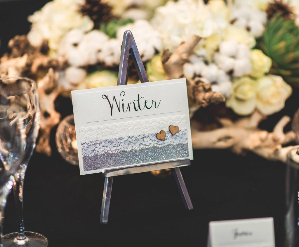 table name decorated with silver glitter lace wooden hearts displayed on small metal easel