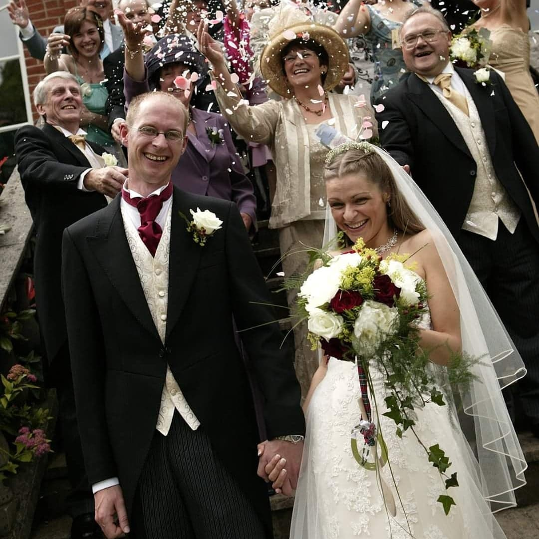 Inspired by Lisa wedding photo bride groom lots of guests throwing confetti and laughing