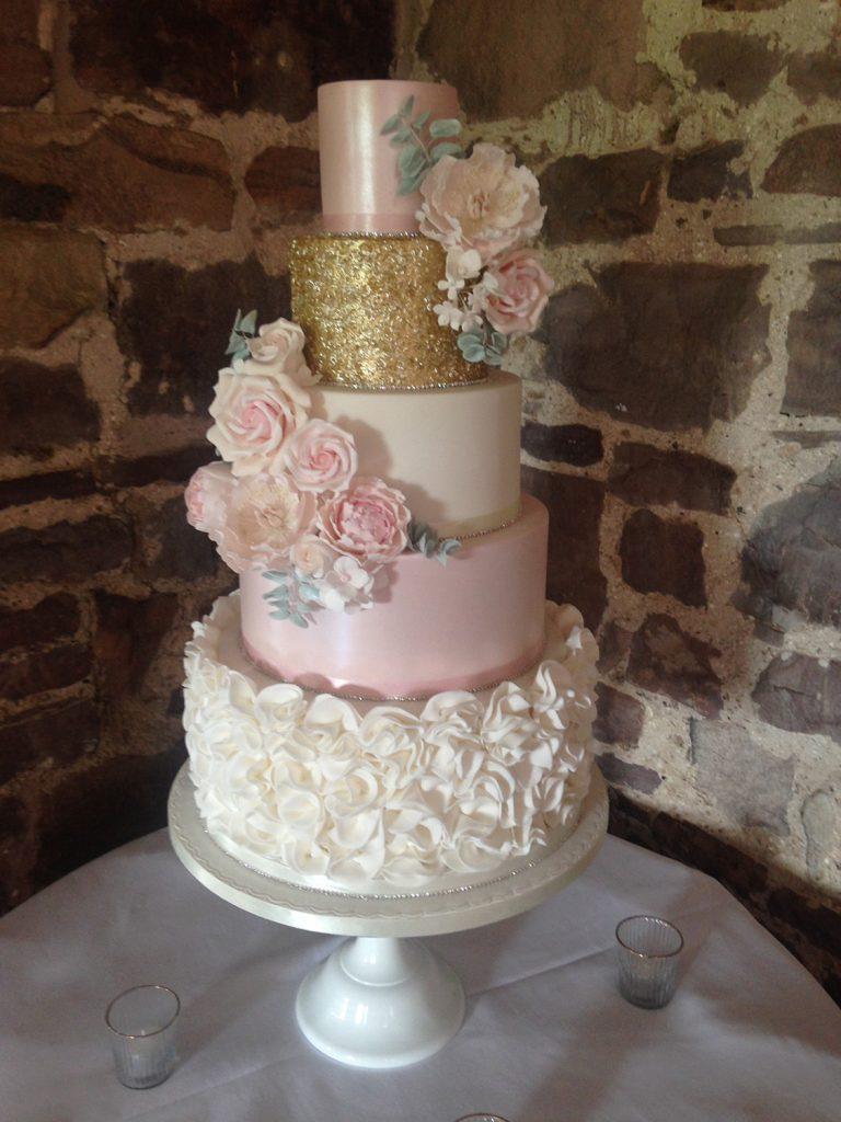 wedding planning 5 tier wedding cake white ruffles rink flowers gold glitter