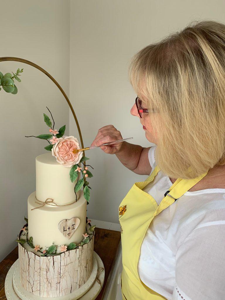 wedding planning lady decorating cake painting sugar flowers