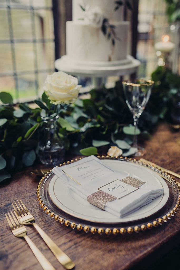 wedding planning table place setting champagne glitter personalised band white napkin menu foliage cake