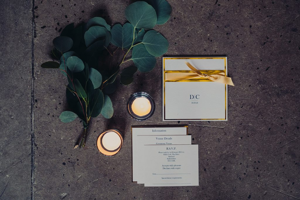 flatlay wedding invites inserts ivory gold foil and ribbon candles foliage on stone floor