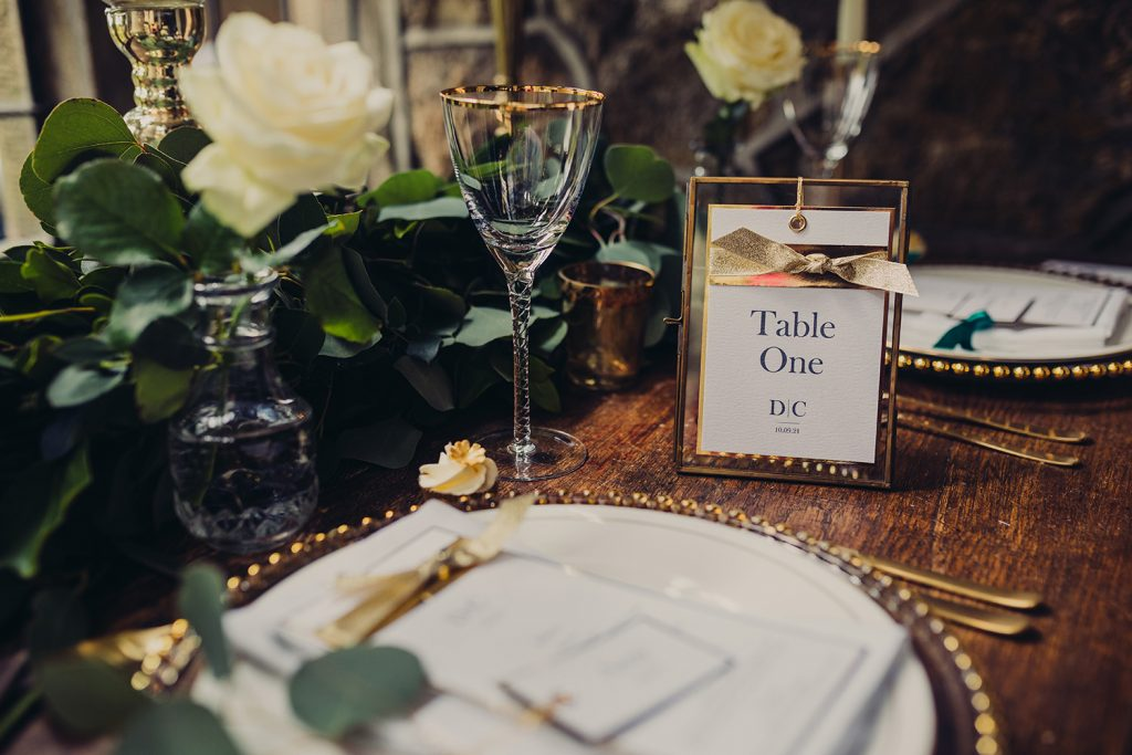 wedding checklist table number gold frame foliage flowers table plate glasses