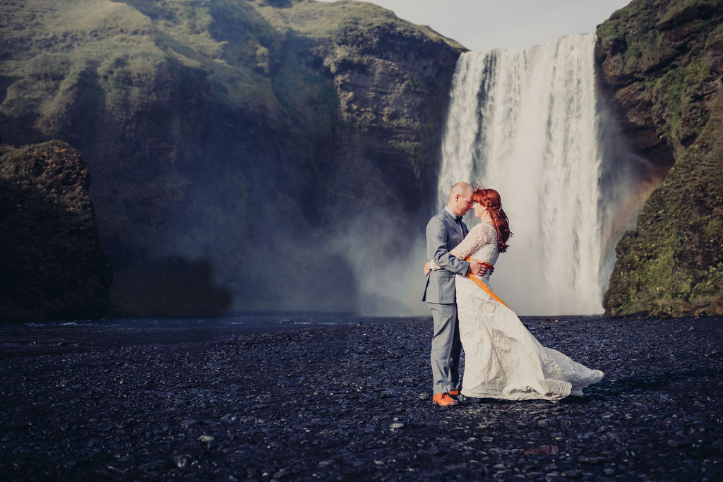 wedding checklist bride and groom embracing waterfall mountains behind
