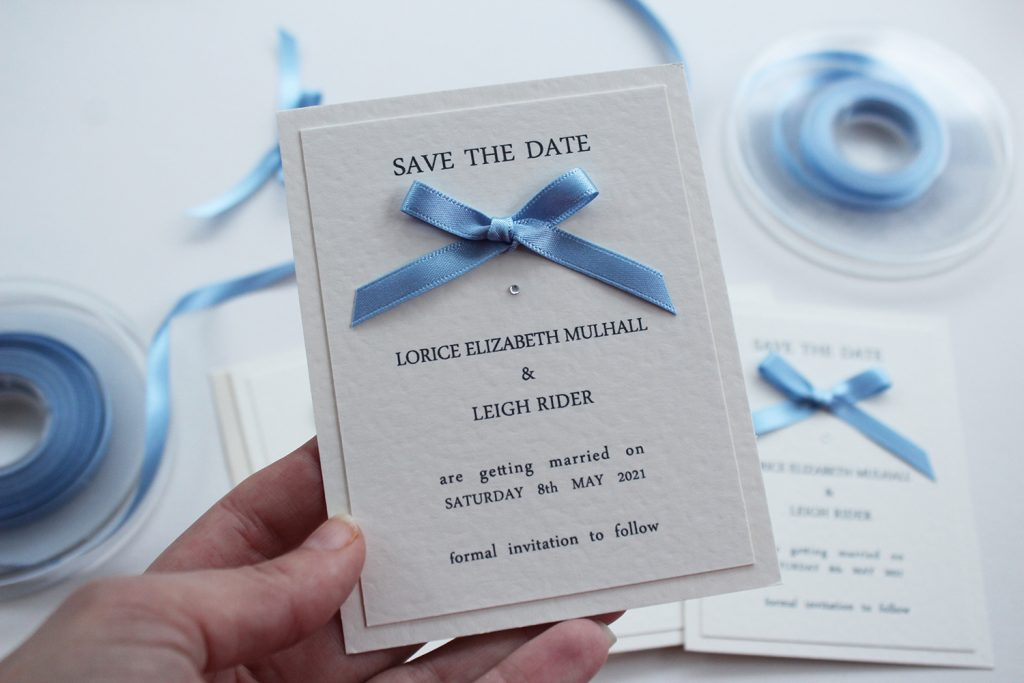wedding save the dates ivory card blue ribbon bow hand held faded background